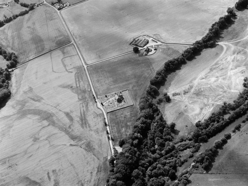 Oblique aerial view centred on the cropmarks of the Roman Temporary Camp, ring ditch and pits with Strathcathro Parish Church adjacent, looking to the WSW.