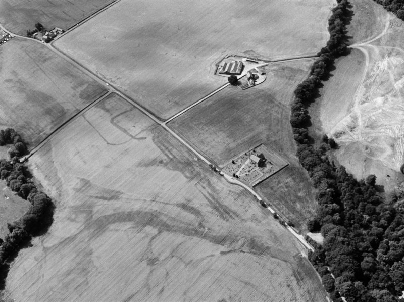 Oblique aerial view centred on the cropmarks of the Roman Temporary Camp, ring ditch and pits with Strathcathro Parish Church adjacent, looking to the W.