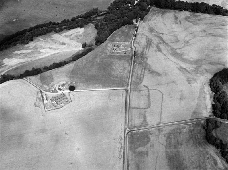 Oblique aerial view centred on the cropmarks of the Roman Temporary Camp, ring ditch and pits with Strathcathro Parish Church adjacent, looking to the NE.