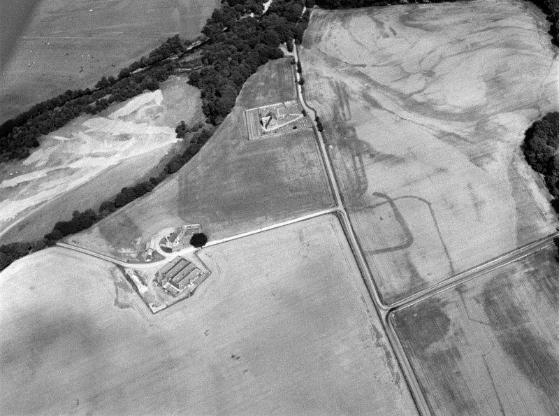 Oblique aerial view centred on the cropmarks of the Roman Temporary Camp, ring ditch and pits with Strathcathro Parish Church adjacent, looking to the E