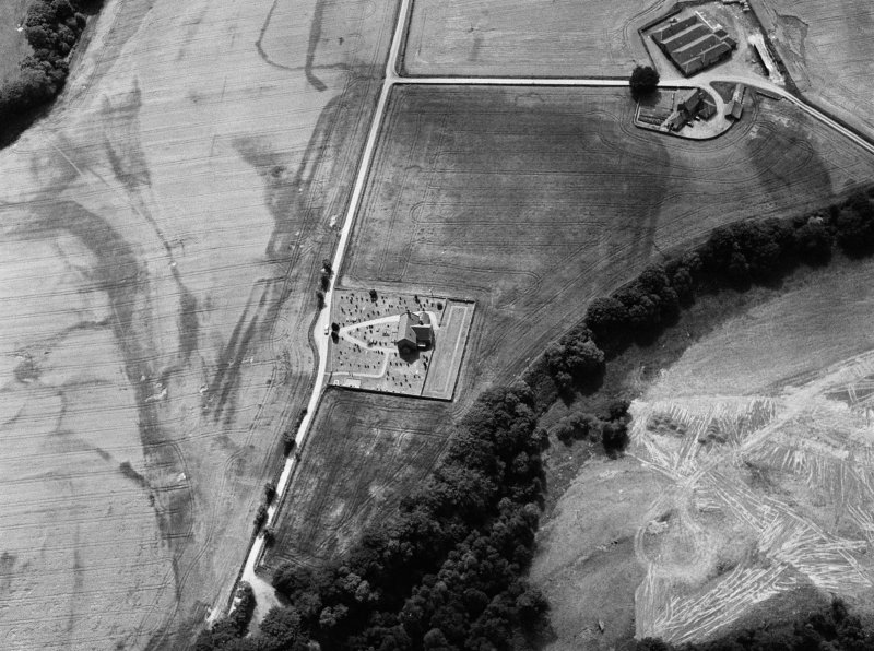 Oblique aerial view centred on the cropmarks of the Roman Temporary Camp, ring ditch and pits with Strathcathro Parish Church adjacent, looking to the SW.