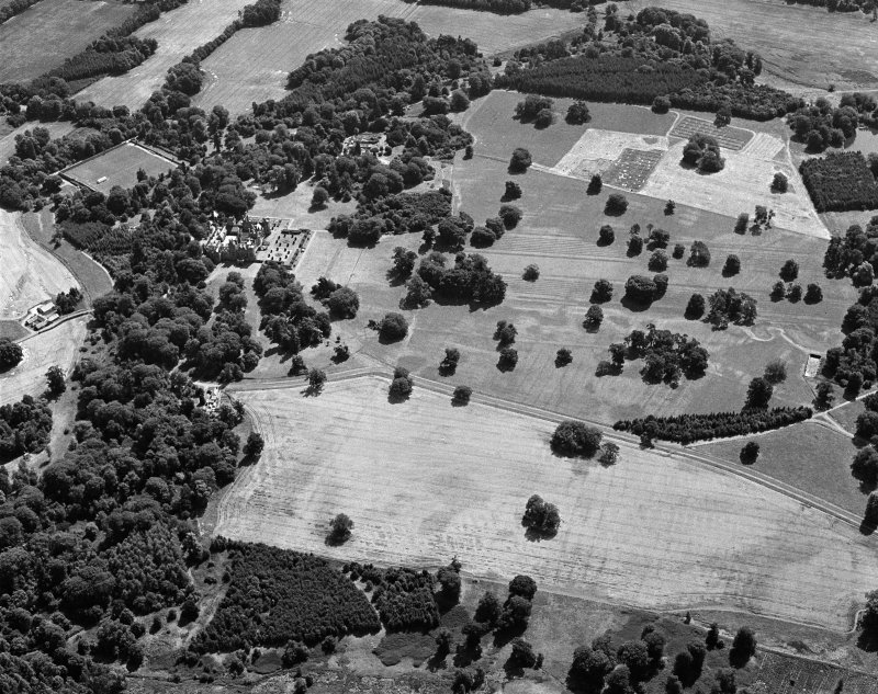 Oblique aerial view centred on the cropmarks of the ring ditches and rig at Kinnaird Park with Kinnaird Castle and Policies adjacent, looking to the SSE.