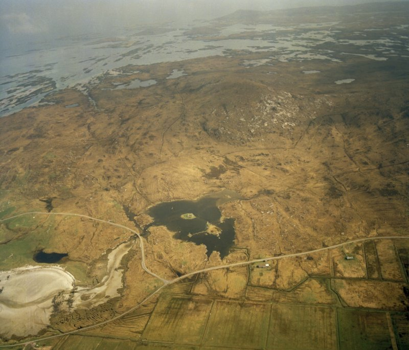 General oblique aerial view centred on the remains of the dun, taken from the NW.