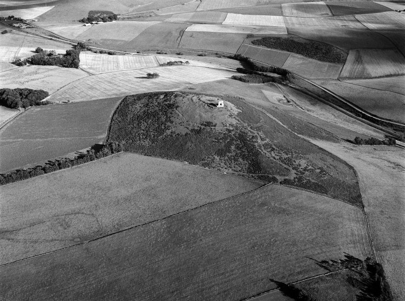 Oblique aerial view centred on the remains of the tower house and fort at Dunideer, looking to the SE.
