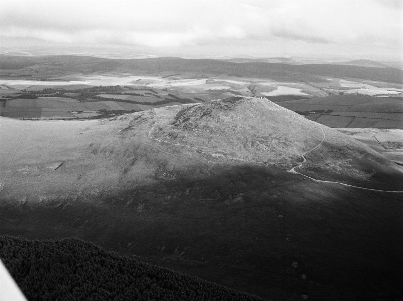 Oblique aerial view centred on the remains of the vitrified fort at Tap O' Noth, looking to the SSE.
