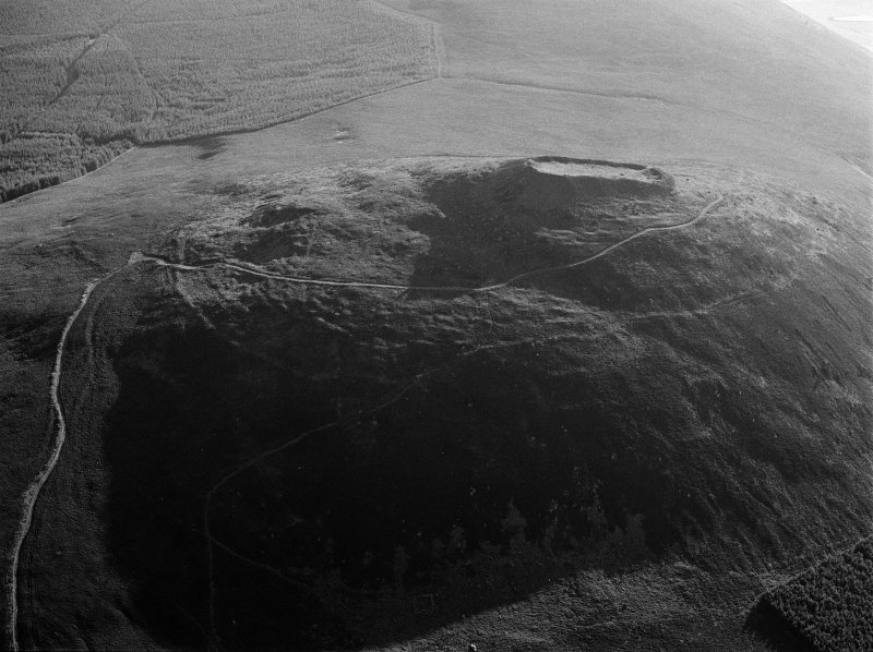 Oblique aerial view centred on the remains of the vitrified fort at Tap O' Noth, looking to the NE.