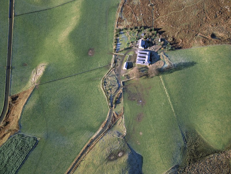 Oblique aerial view centred on the remains of the stone circle with the remains of the township adjacent, taken from the ESE.