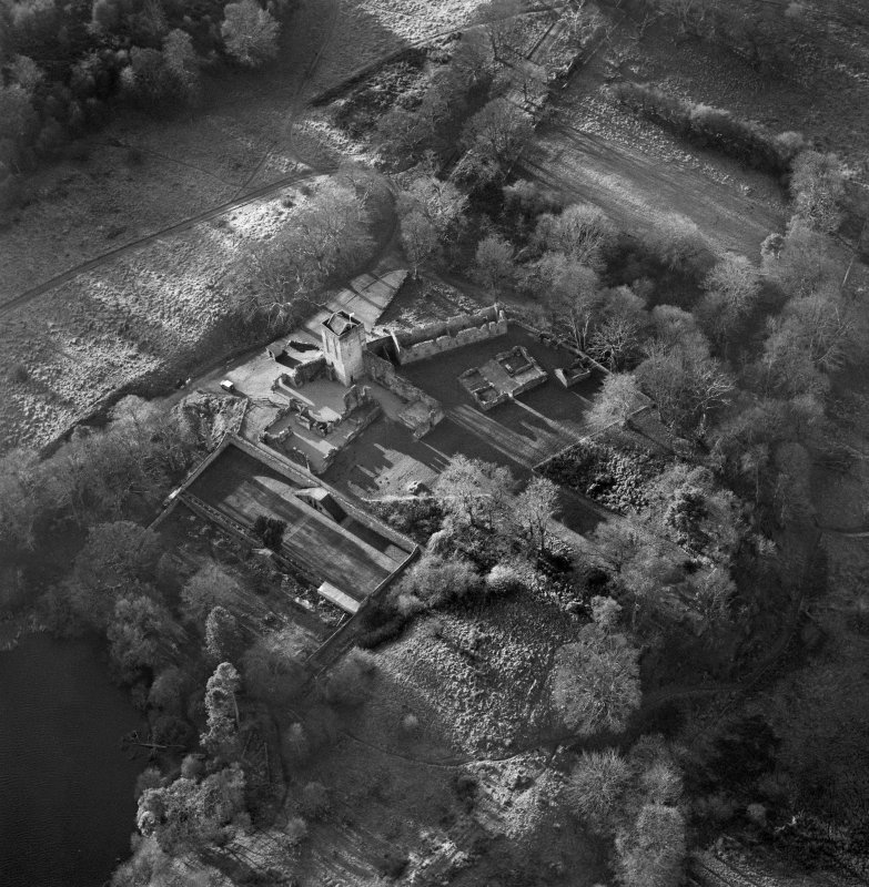 Oblique aerial view centred on the remains of Mugdock castle, chapel and tower, taken from the NE.