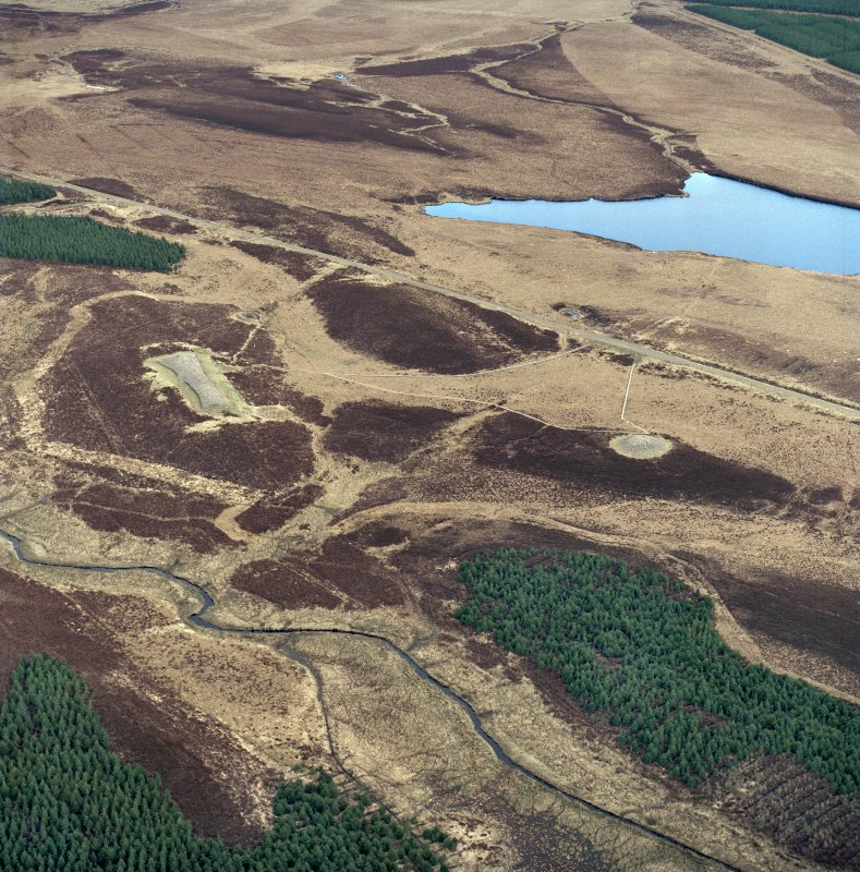 Oblique aerial view centred on the remains of the chambered  cairns, taken from the WSW. Digital copy of photograph.