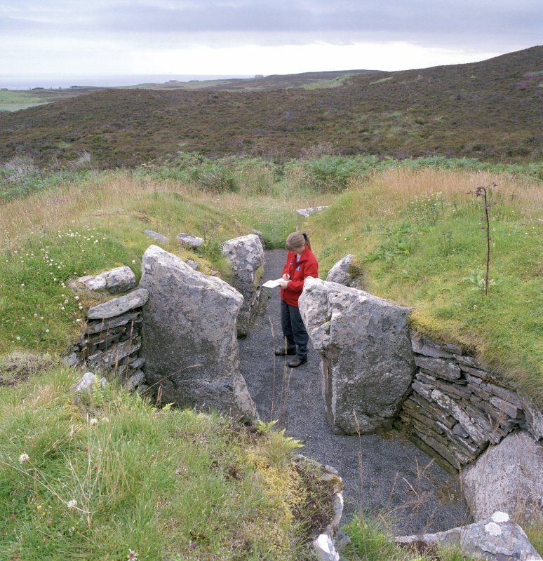 View from N of chamber and passage in chambered cairn; Mrs Angela Gannon (RCAHMS) in picture. Digital copy of photograph.