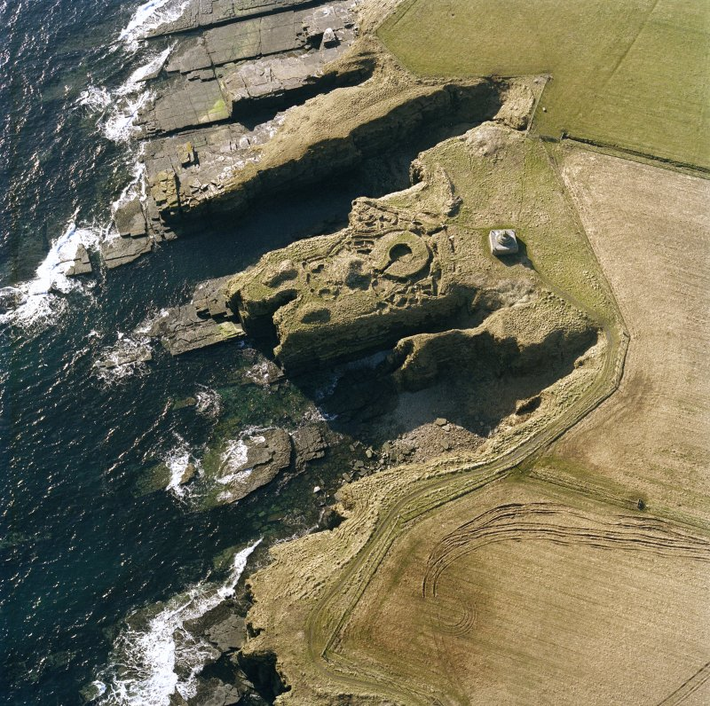 Oblique aerial view of the commemorative monument and the remains of Nybster broch, taken from the N.