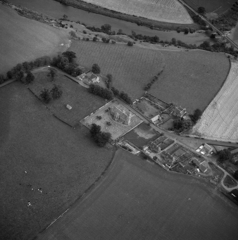 Oblique aerial view centred on church from NW.