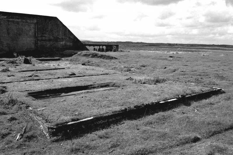 Tain Airfield Tracked target Range. View from NE showing remains of tracked target vehicle shed/building with section of track still in situ.