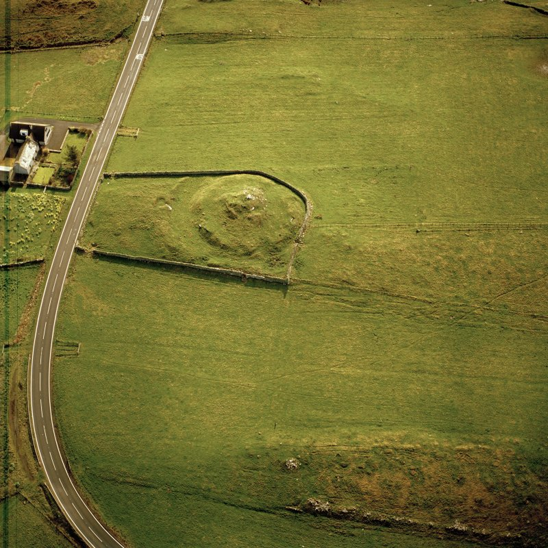 Oblique aerial view centred on the remains of the broch taken, from the WNW.