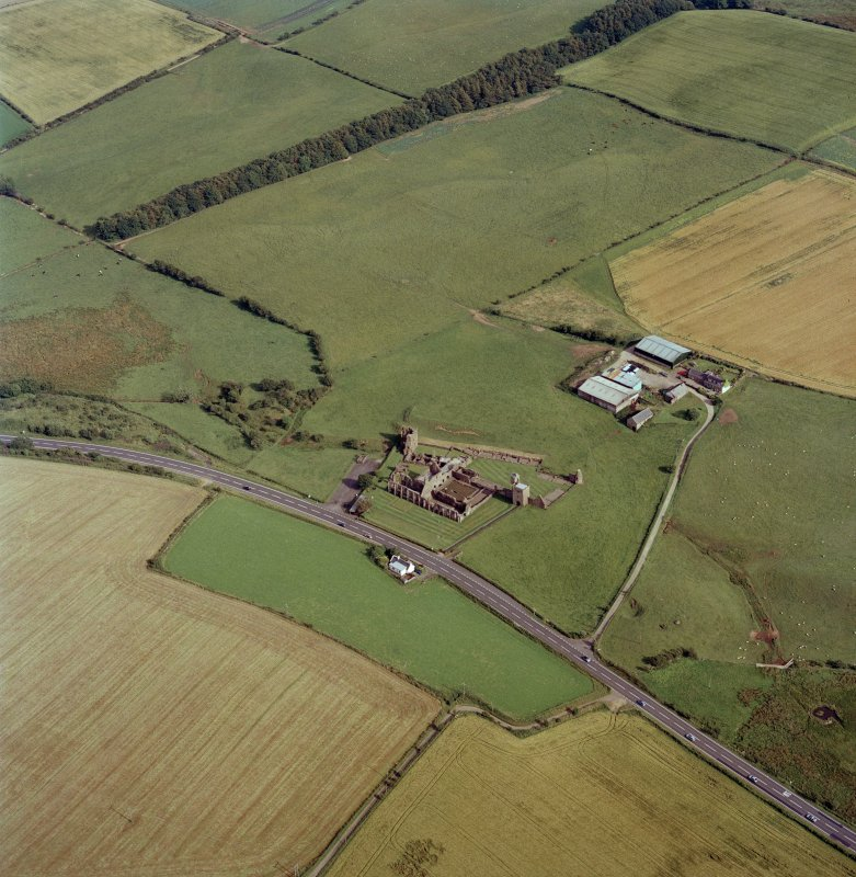 Oblique aerial view centred on the farmsteading and the remains of the abbey, taken from the NW.