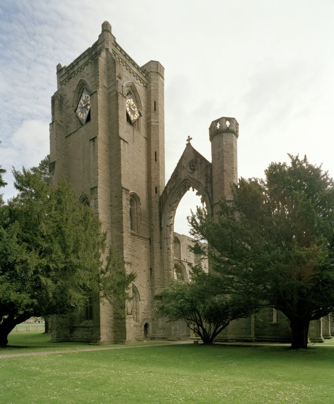 View of bell tower with clock and remains of tracery window from SW