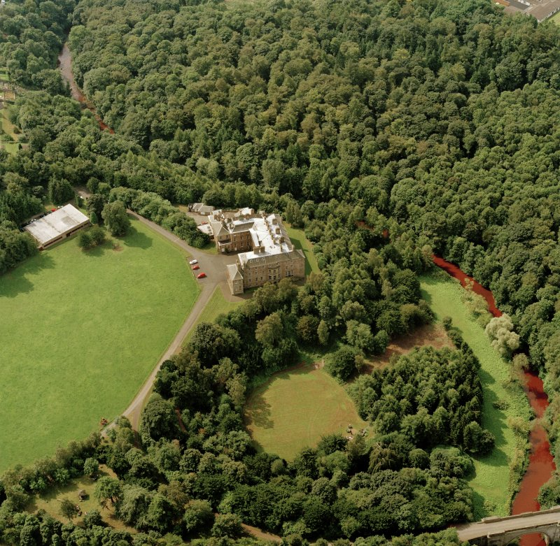 Oblique aerial view centred on the country house and garden with bridge adjacent, taken from the NE.