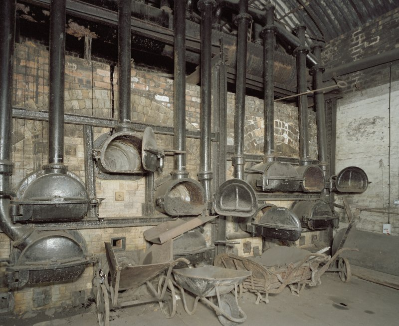 Interior. Retort House: View of retort benches 1 and 2 from NW with coal handling artefacts in foreground.