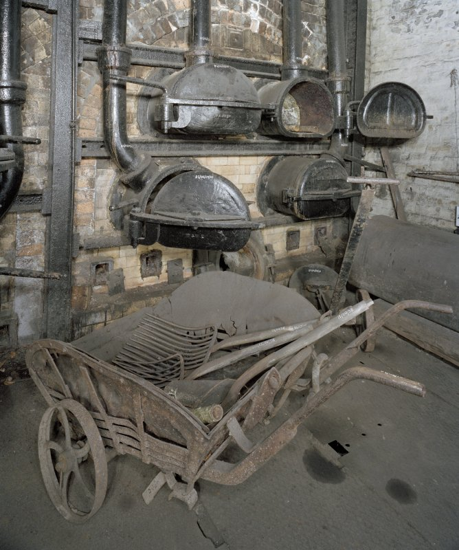 Interior. Retort House: View of retort bench 2 and spent coke handling equipment. Note the cast iron retort doors and the neck of the ceramic tube in which the coal is heated can be seen.