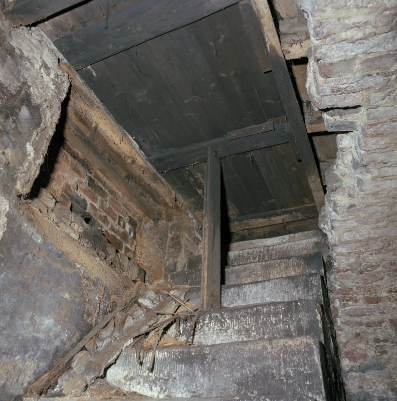 Scanned image of Interior.  Detail of stone access steps from ground floor through wooden door as hatch.