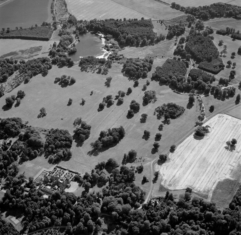 Oblique aerial view centred on the cropmarks of avenues leading to the country house, taken from the NNE.