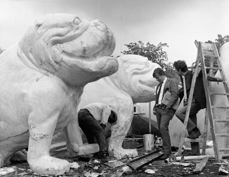 View of John Wells and John Cox watching workmen put the finishing touches to Bulldogs designed for the Expo '67 exhibition.