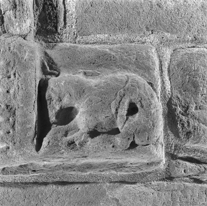 Detail of zoomorphic figure at bottom right hand corner of doorway on W side of tower.