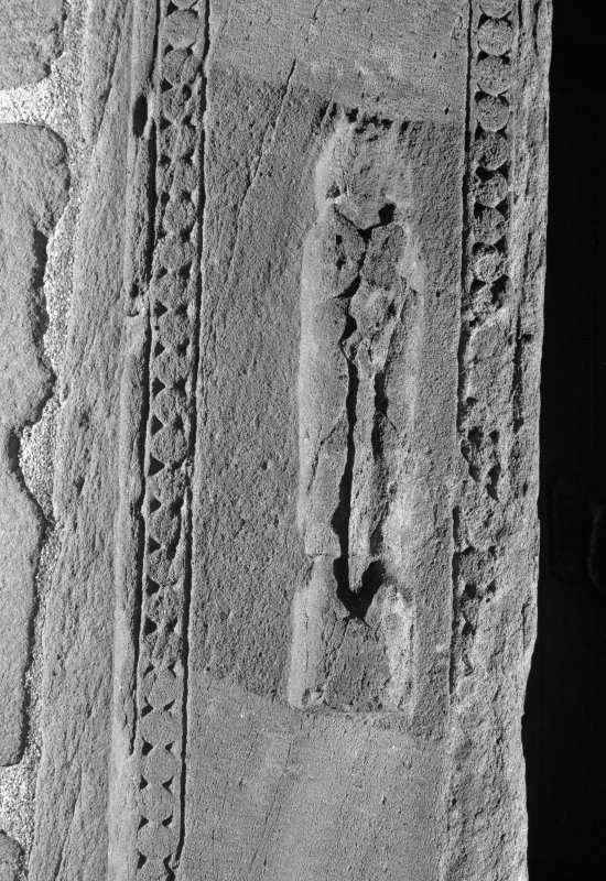 Detail of carved figure to left of doorway on W side of tower.
