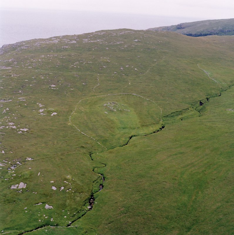 Skipisdale, Mingulay, oblique aerial view centred on the remains of the roundhouse, buildings, field banks and lazy beds, with the settlement mound adjacent and a peat stack stand in the foreground, taken from the E.