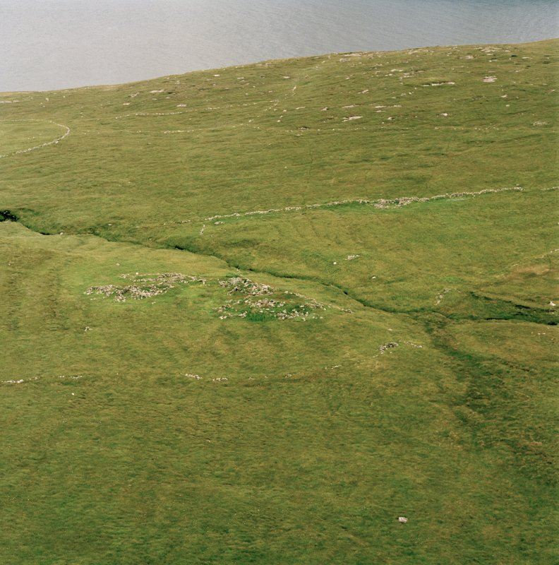 Skipisdale, Mingulay, oblique aerial view centred on the remains of the roundhouses and buildings with the enclosures and lazy beds adjacent, taken from the E.