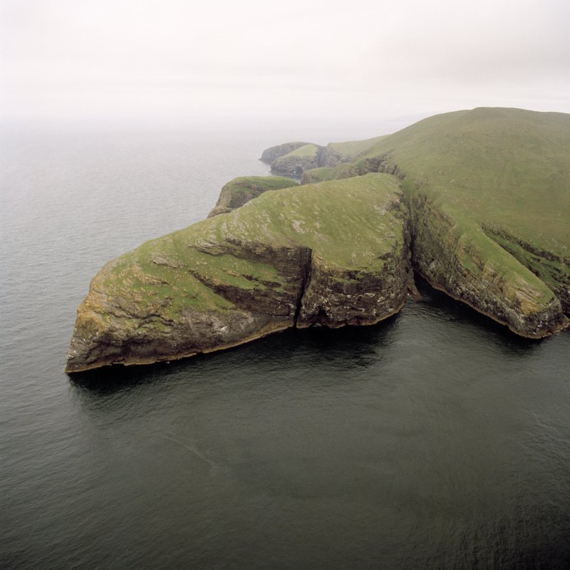 General oblique aerial view centred on the remains of Dun Mhiughlaigh promontory fort, Mingulay, with coastal promontories and sea stacks adjacent, taken from the SSW.