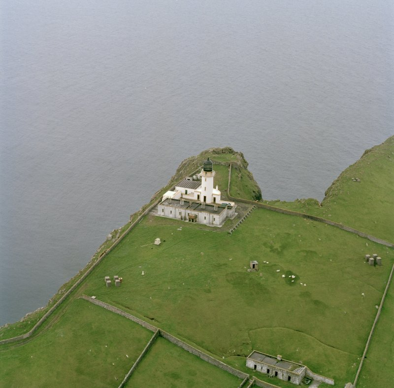 Oblique aerial view centred on Barra Head lighthouse, Berneray, with the remains of the dun adjacent, taken from the ENE.