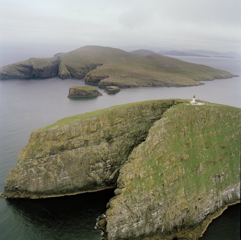 Oblique aerial view of Barra Head lighthouse, Berneray, with the island of Mingulay and those to the N in the background, taken from the SSW.