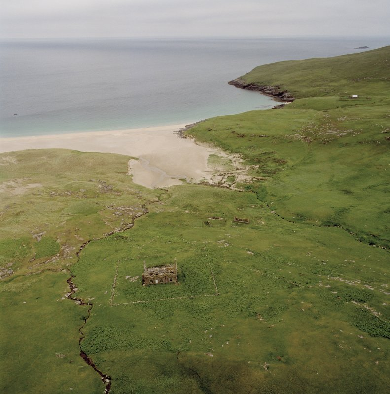 Mingulay, oblique aerial view centred on the remains of the chapel house and enclosure with the remains of the township, chapel and graveyard and the school and schoolroom adjacent, taken from the NW.