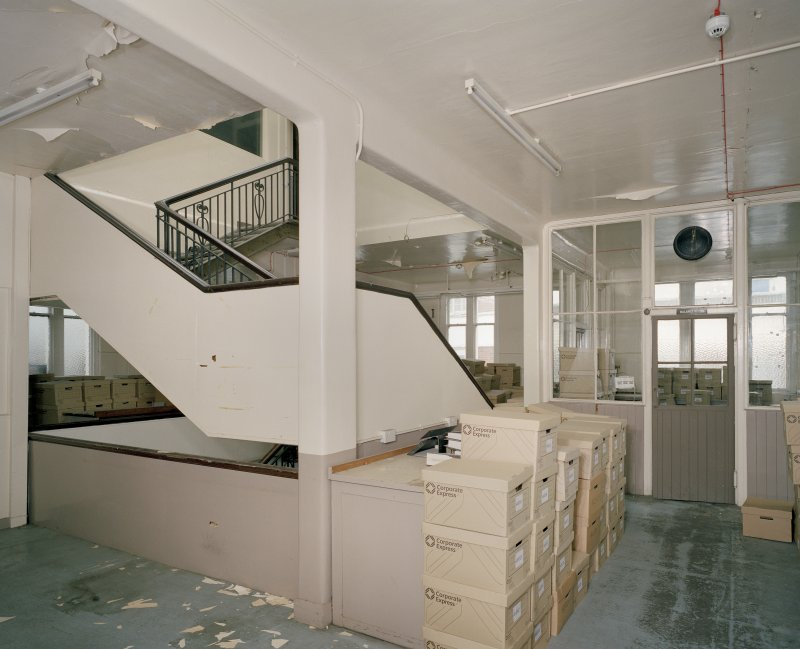 Interior. Laboratory Building, 1st floor, central staircase and lab beyond. There are 2 laboratory areas on this floor, on elaboratory area with secure room on third, together with two fume cupboards on 1st floor.