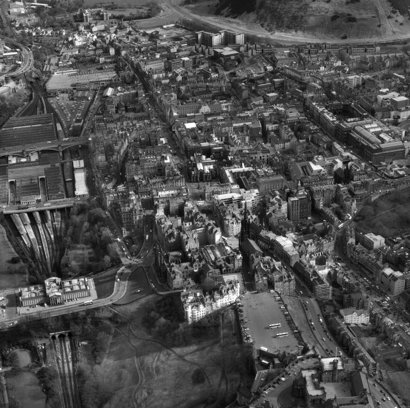 Oblique aerial view of centre of Edinburgh including Esplanade at The Castle in foreground, looking down High Street towards Holyrood Palace, with The Mound and the National Gallery for Scotland on left of photograph and Old College and The National Museum of Scotland on right