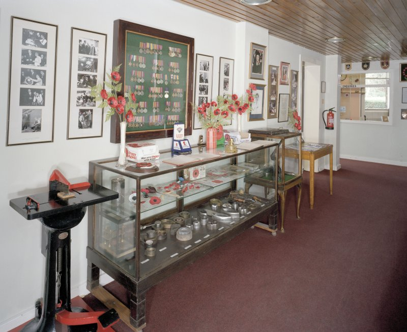Interior. Ground floor, passage showing display cabinet with historic poppy cutting moulds.