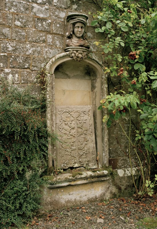 Detail of niche in wall of formal garden with carved head above and stone fragment inside.