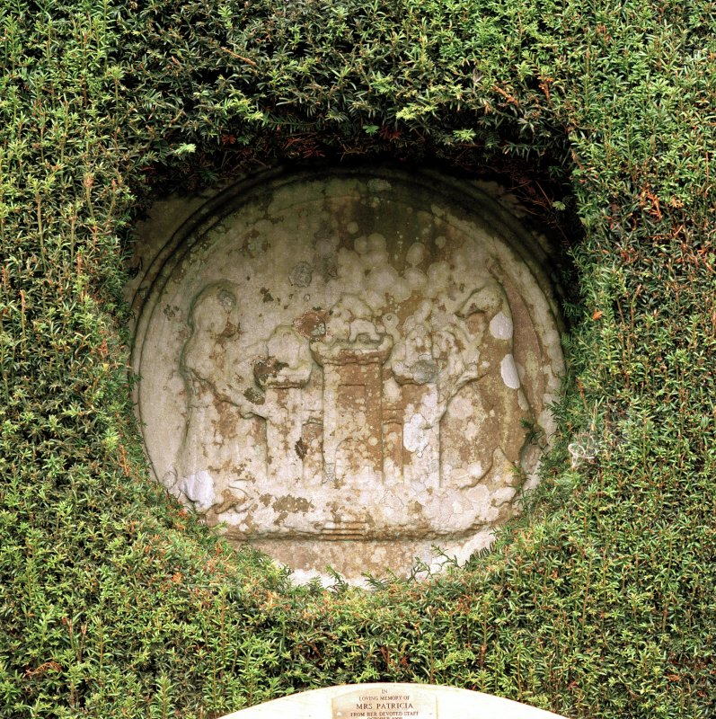 Detail of stone roundel set into wall of formal garden.