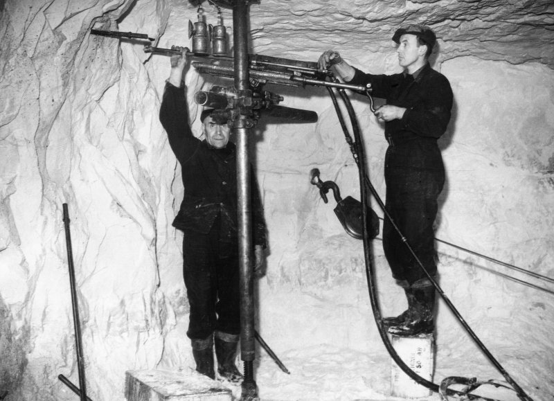 Scanned copy of view showing miners drilling the working face below ground using an hydraulic drill in advance of placing explosive charges.