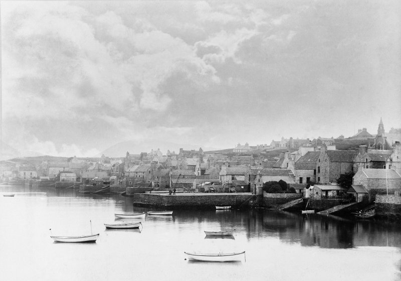 Scanned image of photograph showing a general view of Stromness piers and harbour from mid-way along the town shore, taken from the N and looking S to Hoy.