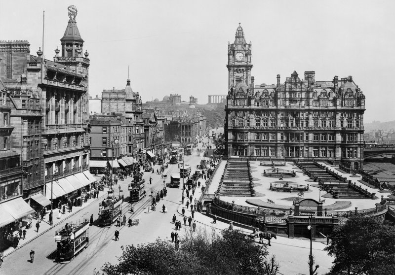 View from Scott Monument, Edinburgh looking east towards Calton Hill showing the North British Hotel, Waverley Gardens and a busy Princes Street with shop awnings, pedestrians, trams, buses and horse and carts.