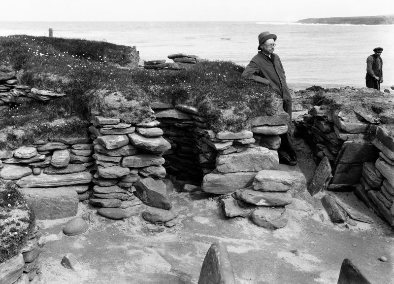 Excavation photograph showing Vere Gordon Childe at Hut 4 Door and cell 2, Skara Brae.