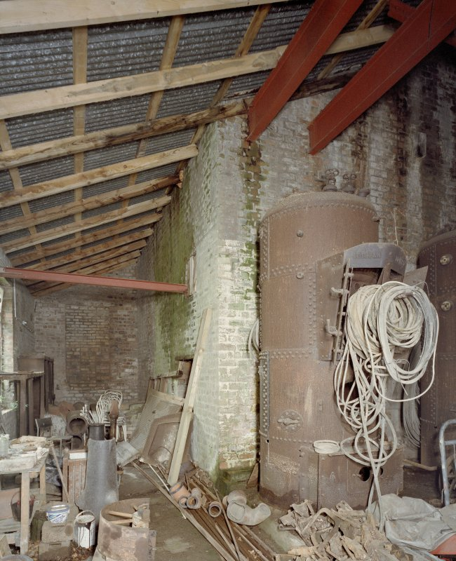 Interior. View looking towards the fly wheel of the pan house crusher in background. This area is now used as a work shop/storage area by the musuem. The Boiler on the right is from another site.