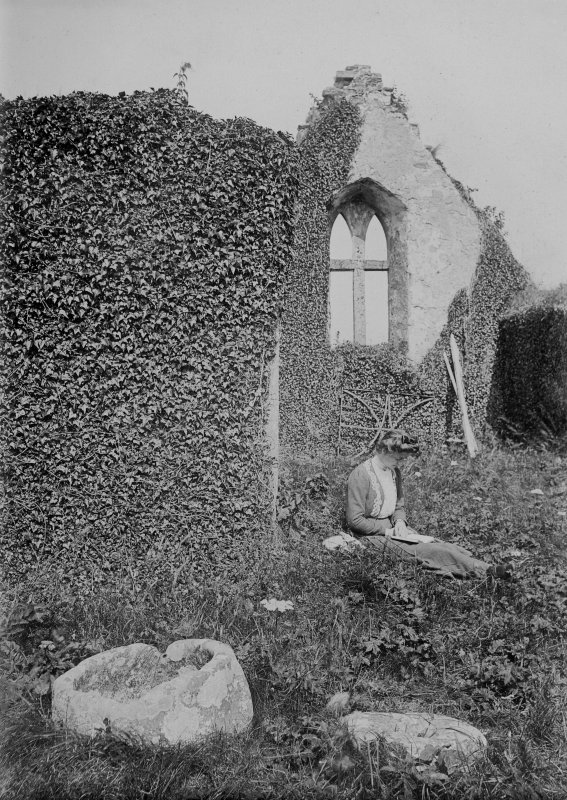 Digital copy of general view of interior of Durness old parish kirk, looking from the N aisle towards the E gable. A lady is seated, reading, in the middle ground. The old font lies in the foreground. From photographic print included in A O Curle's 'Sutherland' journal (MS 36/9, loose at page 88).