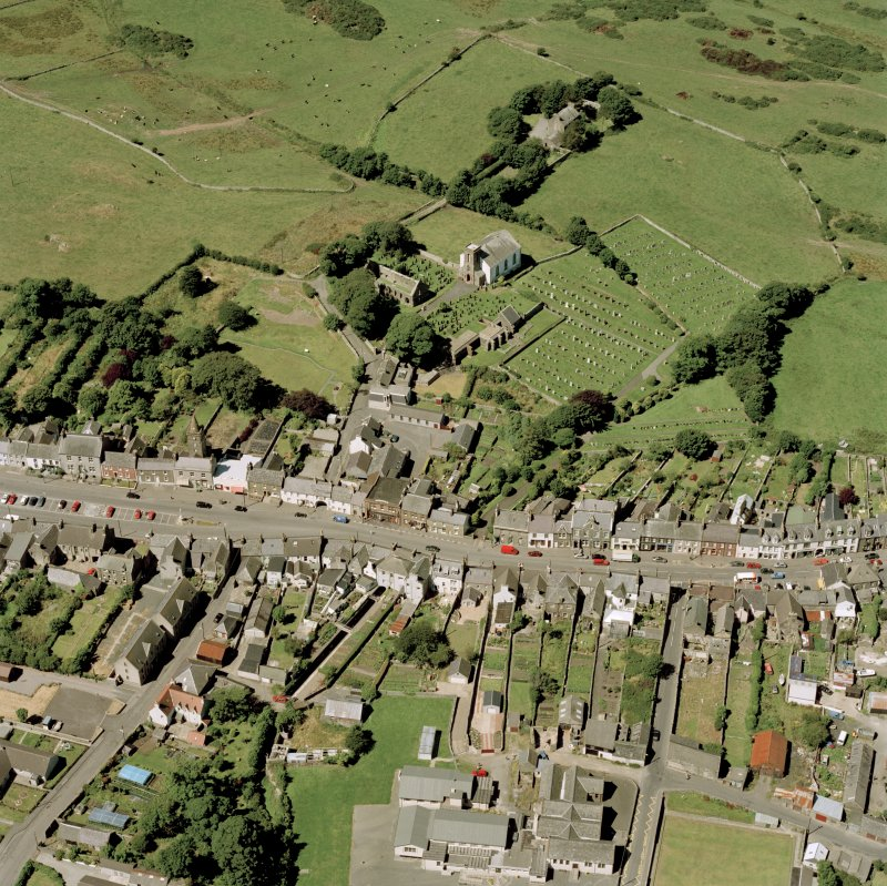 Oblique aerial view of Whithorn centred on the church, burial ground, manse and the remains of the priory, taken from the ESE.