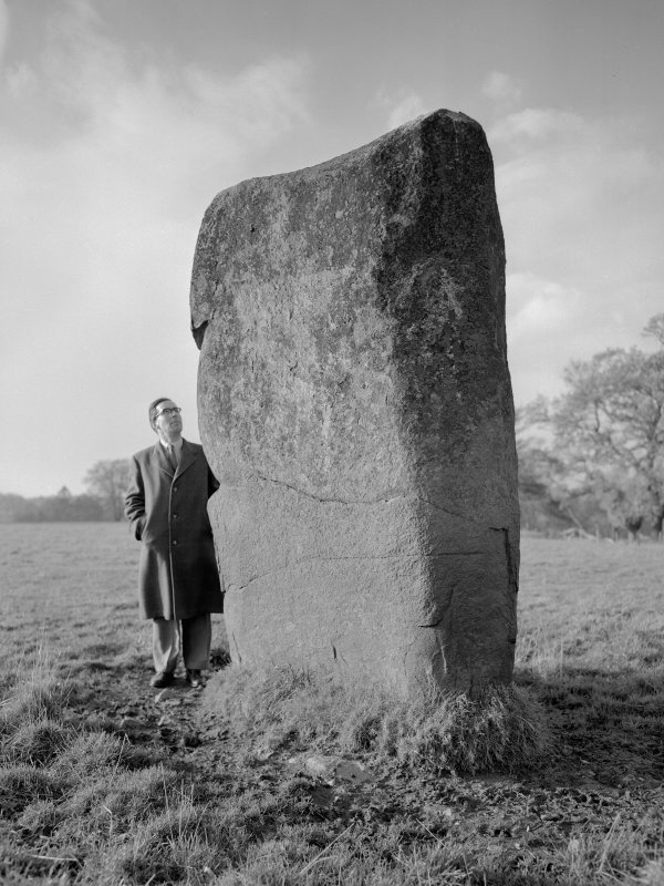 Scanned image of view of standing stone from south-east, with Mr Alastair Maclaren (RCAHMS).
