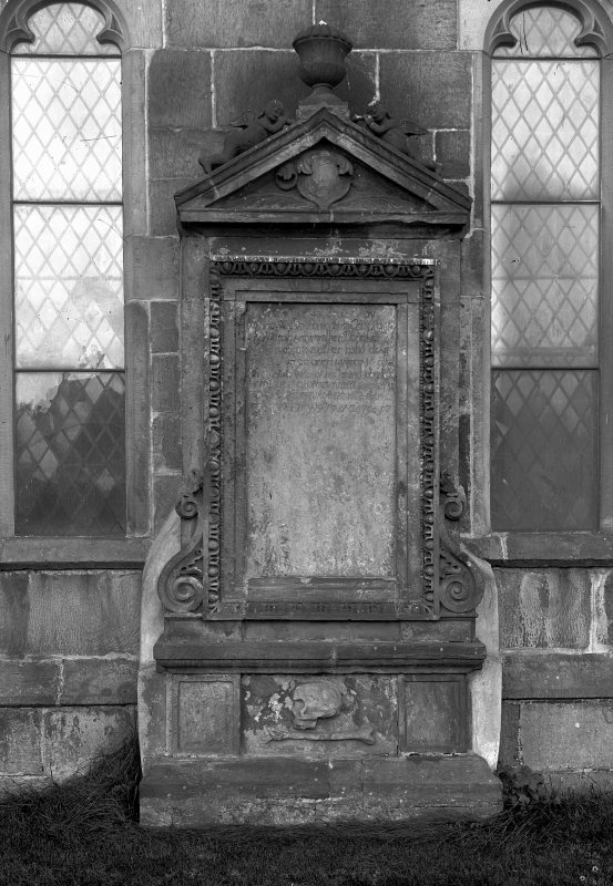 Edinburgh, Kirk Loan, Corstorphine Parish Church. View of large memorial against the wall of the Church. An inscribed panel with two angels blowing trumpets and an urn on the pediment, with a crest below. The tablet rests on scrolled supports and has a relief of a skull and bone in a panel below.