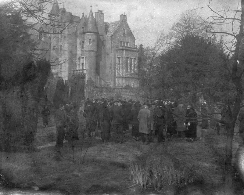 General distant view of the house partially obscured by trees with a large group of people walking around the grounds, seen from the South.