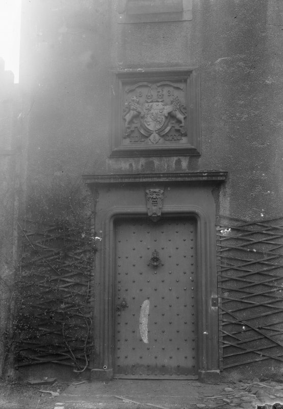 Detailed exterior view of the entrance doorway seen from the West North West. Above the studded door is a stone relief of a coat-of-arms of two lions flanking a crest dated 1831 and with the initials  ...
